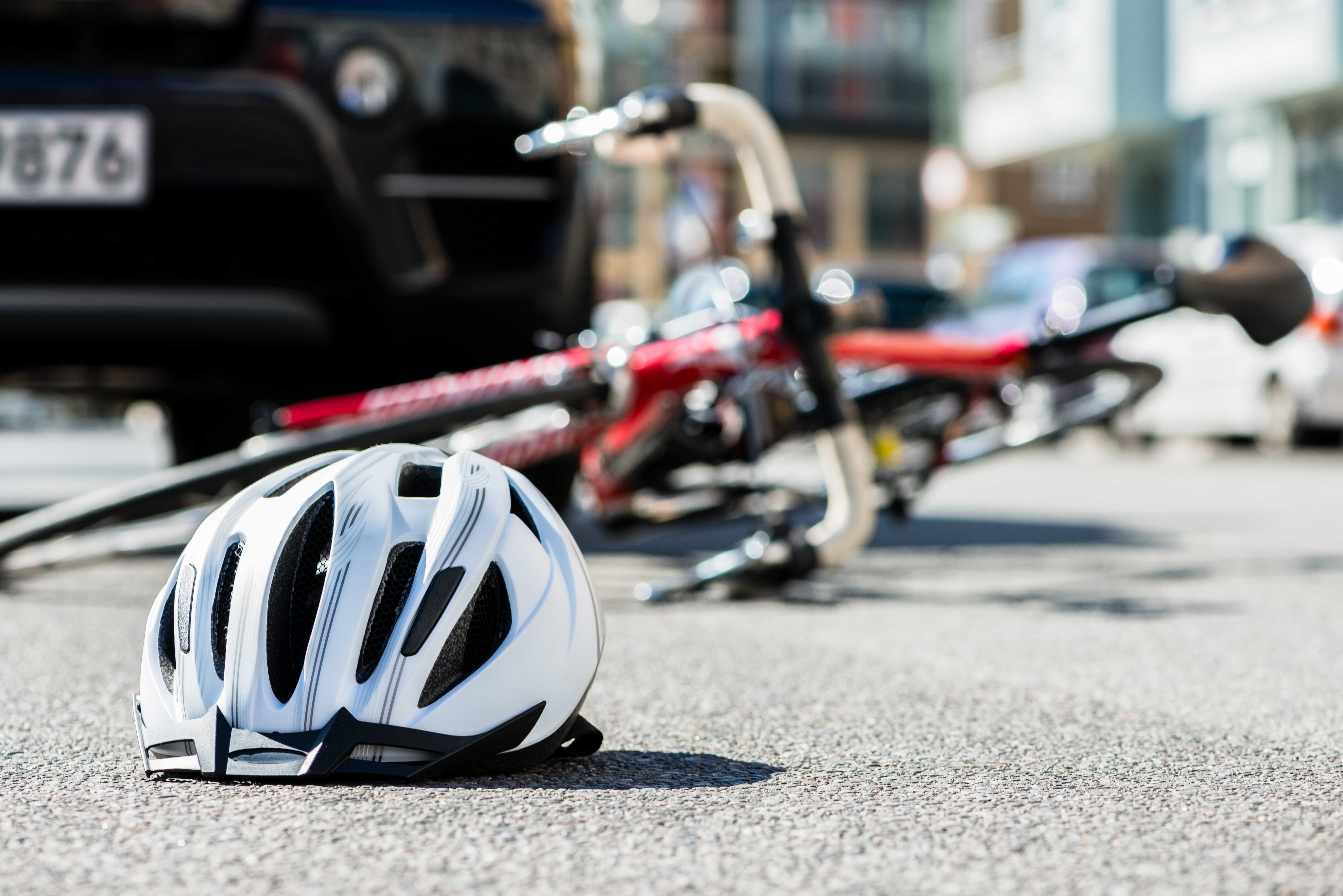 white bicycle helmet in front of overturned bicycle